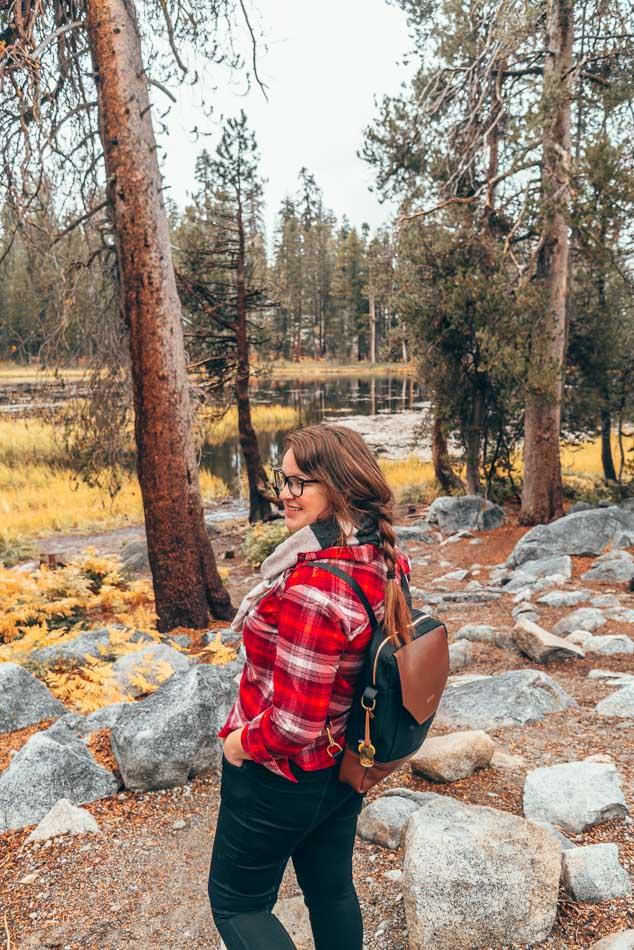 Exploration du parc national de Yosemite en automne avec une chemise en flanelle rouge, une écharpe et un sac à dos.
