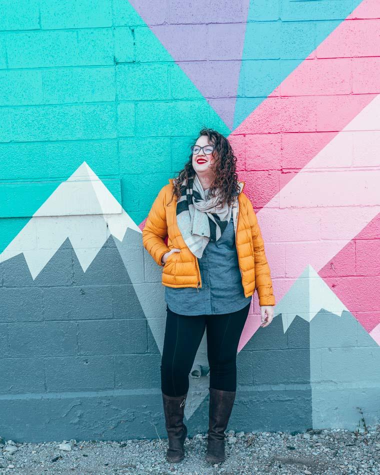 Lia en doudoune devant une peinture murale de montagne à Salt Lake City, Utah.