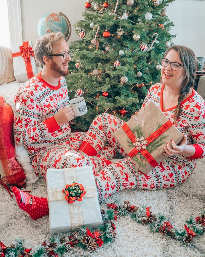 Lia et Jeremy en pyjama de Noël assorti devant un sapin de Noël.